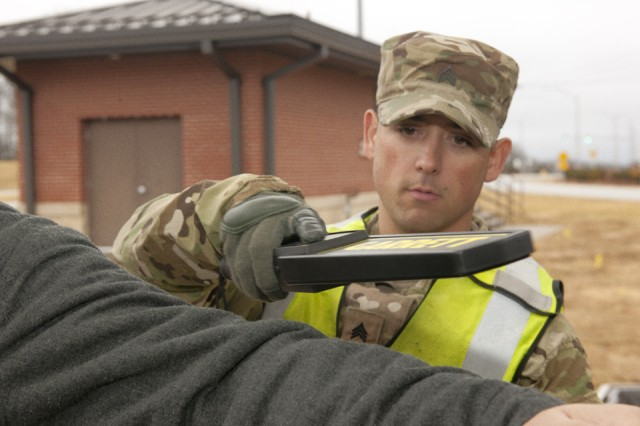 Sgt. Jacob Schoendienst, Company B, 1st Battalion, 138th Infantry Regiment, Missouri National Guard, runs a metal detector over a driver who was stopped for a vehicle inspection Monday.