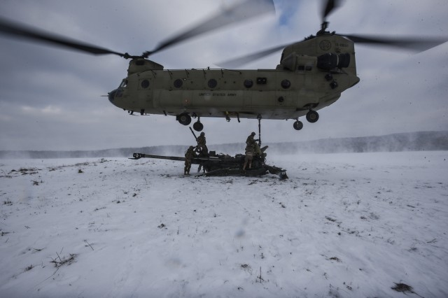 "Field Artillerymen from Cobra Battery, Field Artillery Squadron, 2nd Cavalry Regiment, stand ready to secure their M777 Howitzer to a CH-47 Chinook Helicopter from Bravo Company, 1st Battalion, 214th Aviation Regiment, 12th Combat Aviation Brigade, ""Big Windy,"" during environmental qualifications and sling-load training Jan. 18, 2017, outside Grafenwoehr, Germany."
