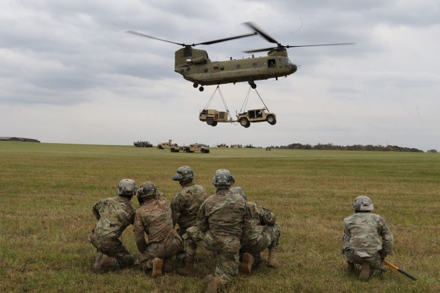 Although this is not an actual Tactical Communications Node-Lite (TCN-Lite) being sling loaded and was not part of the developmental test, the vehicle and trailer are of similar proportion. Soldiers from the 1st Brigade Combat Team, 101st Airborne (Air Assault) Division sling load a High Mobility Multipurpose Wheeled Vehicle and trailer during field exercises in November 2016 at Fort Campbell, Kentucky. (U.S. Army photo courtesy of 1/101st ABN Div)