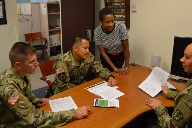 Capt. Raven Cornelius, contract specialist, Army Contracting Command-Warren-Intelligence and Security Command (INSCOM), briefs INSCOM Acquisition Center staff members (left to right) Sgt. 1st Class John Wysocki, Maj. Ryan Ocampo, and Betty Jarman.