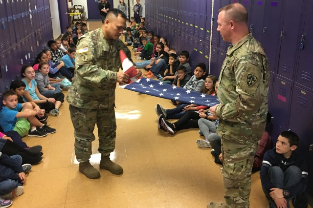 Sgt. 1st Class Benito Santos (left), and Sgt. 1st Class Jay Alan Ottinger, both research development test and evaluation (RDT&E) non-commissioned officers with Operational Test Command's Maneuver Test Directorate (MTD), show how to fold a flag during flag etiquette training for fifth-graders at Florence Elementary School, Florence Texas, on Jan. 20, 2017.