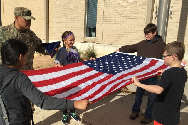 Sgt. 1st Class Benito Santos, a research development test and evaluation non-commissioned officer in Operational Test Command's Maneuver Test Directorate, trains fifth-graders how to unfold the flag at Florence Elementary School, Florence Texas, on Jan. 20, 2017.