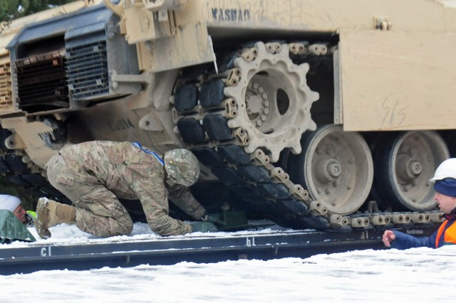 ZAGAN, Poland - A Soldier assigned to 1st Battalion, 66th Armored Regiment, 3rd Armored Brigade, 4th Infantry Division, places a chop block under the tread of an M1A2 Abrams Tank Jan. 25, 2017. The chop block secures the tank and prevents it from moving forward as it is transported via rail to Grafenwoehr, Germany where it will be used by the Soldiers as they conduct training in Europe as part of Operation Atlantic Resolve. The tanks arrived in Poland earlier this month from the United States and were offloaded to be test fired before moving onto Germany. The movement of equipment and troops into and around Europe kicks off what will be a continuous rotation of armored brigades from the United States as part of Operation Atlantic Resolve. The Iron Brigade's move to Germany will enhance deterrence capabilities in the region and improve the U.S. ability to respond to potential crisis and defend its allies and partners within the European community.