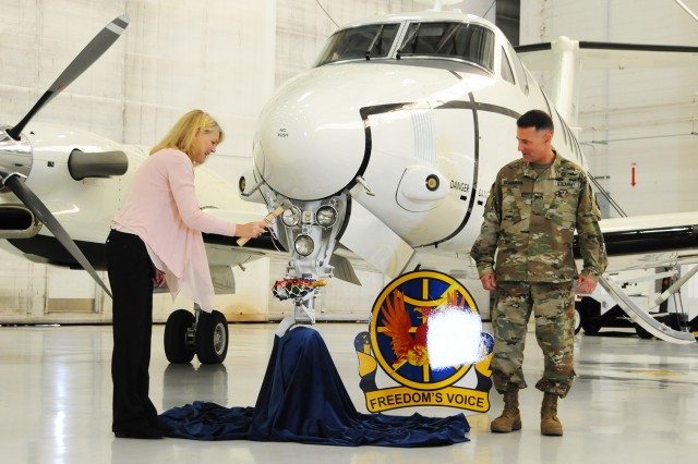 Kathy Roland, wife of CW5 Joseph B. Roland, chief warrant officer of the Aviation Branch, christens the newly acquired C-12S aircraft with the help of Col. Michael E. Demirjian, ATSCOM commander, during a ceremony at Cairns Army Airfield Jan. 20.