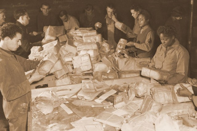 French civilians and Soldiers from the 6888th Central Postal Directory Battalion sort mail in the spring of 1945. The only African-American Women's Army Corps unit sent to Europe during World War II, the 6888th was responsible for clearing years' worth of backlogged mail in both England and France. Viewing their jobs as crucial to morale at the front, they processed some 65,000 pieces of mail a shift and worked three shifts a day. At the same time, the Soldiers faced constant prejudice and broke gender and racial barriers.