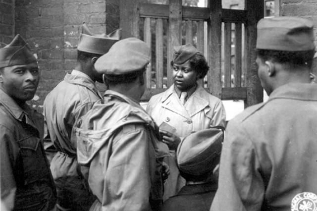"After the 6888th Central Postal Directory Battalion set up its facilities at Rouen, France, it held an ""open house,"" which was attended by hundreds of African-American Soldiers. Pvt. Ruth L. James of the battalion area is on duty at the gate, May 26, 1945. When the 6888th arrived in Rouen in the spring of 1945, it caused a sensation among African-American Soldiers, who were so happy to see girls from home that they crowded the gates daily, causing such a disruption that the battalion sometimes had to call in military police. It had its own MPs, but they were not allowed to carry firearms. Instead, the women learned judo."