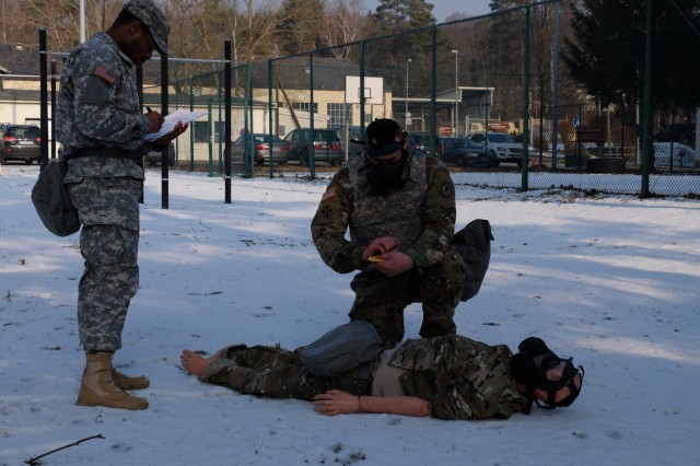 KAISERSLAUTERN, Germany - Sgt. Peter Bickelhaupt, from Headquarters and Headquarters Company, 361st Civil Affairs Brigade, 7th Mission Support Command, right, treats a simulated Chemical Biological Radiological Nuclear casualty during the noncommissioned officer Best Warrior Competition Jan. 23, 2017.