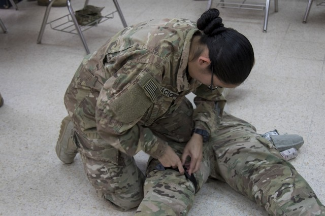U.S. Army Spc. Judith A. Ignacio, of the 369th Sustainment Brigade, demonstrates the proper way to apply a tourniquet during a combat life saver course at Camp Arifjan, Kuwait, Jan. 17, 2017. The course is designed to provide non-medical Soldiers the knowledge they need to provide emergency medical care on the battlefield.