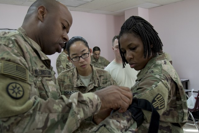 U.S. Army Sgt. 1st Class John L. Wellington demonstrates how to properly apply a tourniquet on Sgt. Tanesha Edwards, both of the 369th Sustainment Brigade, during a combat life saver course at Camp Arifjan, Kuwait, Jan. 17, 2017. The course is designed to provide non-medical Soldiers the knowledge they need to provide emergency medical care on the battlefield. (U.S. Army photo by Sgt. Cesar E. Leon)
