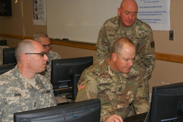 (Left to right) Sgt. 1st Class Kevin Deon, Sgt. 1st Class Matthew Highsmith and Master Sgt. John Gross (standing) work together on the accreditation block of instruction as part of the 80th Training Command's first Quality Assurance Officer course at Grand Prairie, Texas, Jan. 24, 2017.
