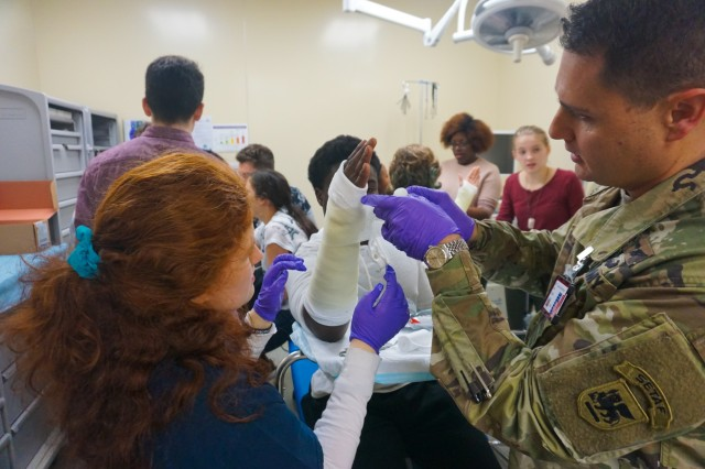 Capt. Jason Auchincloss, U.S. Army Africa Physician Assistant, assists a Vicenza High School student applying a forearm cast during a trip to the Vicenza Army Health Clinic orthopedic and radiology wing Jan. 24, 2017. Vicenza Army Health Clinic leadership and U.S. Army Africa Physician Assistant Capt. Jason Auchincloss invited students from VHS to work alongside U.S. Army medical professionals as part of their human anatomy class.