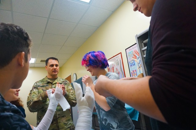 Capt. Jason Auchincloss, U.S. Army Africa Physician Assistant, leads Vicenza High School students through applying a forearm cast during a trip to the Vicenza Army Health Clinic orthopedic and radiology wing Jan. 24, 2017. Vicenza Army Health Clinic leadership and U.S. Army Africa Physician Assistant Capt. Jason Auchincloss invited students from VHS to work alongside U.S. Army medical professionals as part of their human anatomy class.