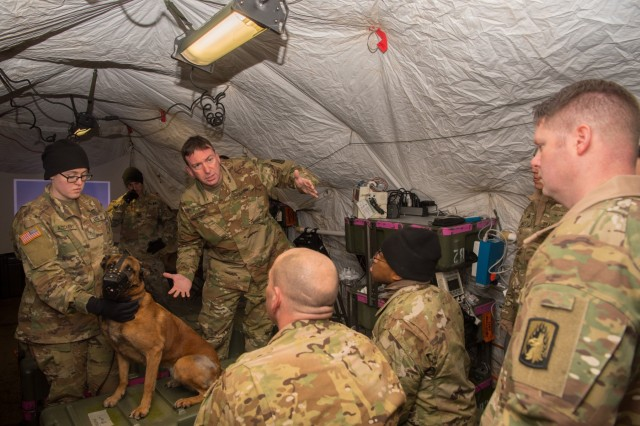 GRAFENWOEHR, Germany - Maj. Christopher C. Corrie, veterinarian, 64th Medical Detachment Veterinary Services Support, provides a class on physical examination, with the assistance of Pvt. Second Class Molly Reichert, a military working dog handler and MWD Anouska of the 100th Military Working Dog Detachment, Jan. 10, 2017.  (U.S. Army Photo by Maj. Chris Angeles, 67th Forward Surgical Team)