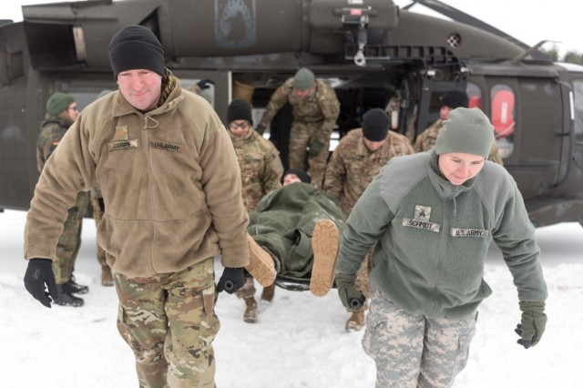 GRAFENWOEHR, Germany - As part of cold-load training being provided by crewmembers of C Company 1-214th General Support Aviation Battalion, Maj. Christopher C. Corrie and Sgt. Holly J. Schmidt of the 64th Medical Detachment Veterinary Services Support, Maj. Linda C. Benavides and Sgt. First Class David A. Thompson, of the 67th Forward Surgical Team, perform a four-person litter carry of Cpt. Aaron J. Vandenbos of the 67th Forward Surgical Team from a UH-60A/L Blackhawk helicopter, Jan. 10, 2017. (U.S. Army Photo by Maj. Chris Angeles, 67th Forward Surgical Team)