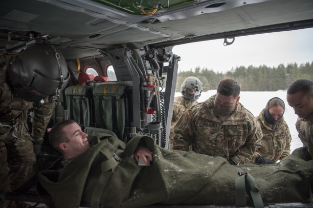 GRAFENWOEHR, Germany - Spc. Nicholas R. Pflug, is unloaded from a UH-60A/L Blackhawk Helicopter by fellow members of the 67th Forward Surgical Team, Spc. Brandon M. Morales, Sgt. Heather L. Wiley, and Spc. Branden R. Baldwin as Staff Sgt. Nestor A. Genuino and Sgt. Alejandro Arredondo of C Company 1-214th General Support Aviation Battalion observe, Jan. 10, 2017.  (U.S. Army photo by Maj. Chris Angeles, 67th Forward Surgical Team)