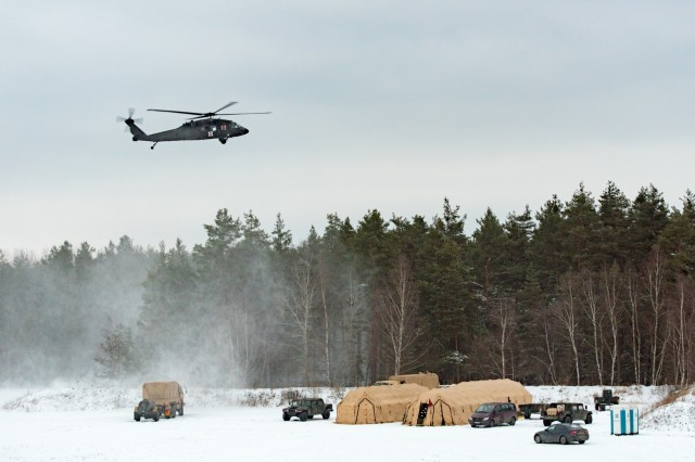 GRAFENWOEHR, Germany - A UH-60A/L Blackhawk helicopter from C Company, 1-214th General Support Aviation Battalion flies above the tents and vehicles of the 67th Forward Surgical Team, Jan. 10, 2017. (U.S. Army Photo by Maj. Chris Angeles, 67th Forward Surgical Team)