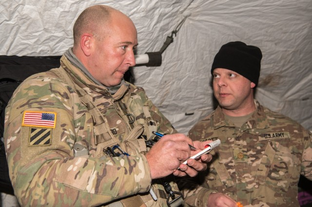GRAFENWOEHR, Germany - Sgt. Chad F. Salinero, a flight medic with C Company, 1-214th General Support Aviation, receives report about a simulated casualty from Maj. Joshua A. Scott, a general surgeon with the 67th Forward Surgical Team, prior to aeromedical evacuation, Jan. 11, 2017.  (U.S. Army Photo by Maj. Chris N. Angeles, 67th Forward Surgical Team)