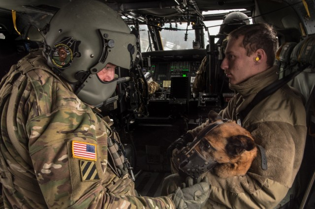 GRAFENWOEHR, Germany - Sgt. Chad F. Salinero, a flight medic with C Company 1-214th General Support Aviation Battalion, pets MWD Anouska, a Patrol Explosive Detector Dog, during her first helicopter ride as she is held by Sgt. Joseph A. Tucci, a military working dog handler with the 100th Military Working Dog Detachment, Jan. 11, 2017. (U.S. Army Photo by Maj. Chris Angeles, 67th Forward Surgical Team)