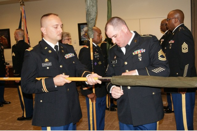 Capt. Dmitry Lavallee holds the staff steady while Sgt. 1st Class John Shields cases and ties the Charlie Company colors at the 4th Battalion, 321st Regiment's deactivation ceremony at Redstone Arsenal, Ala., Dec. 18, 2016. The deactivation is part of the 800th Logistics Support Brigade restructuring, which is a result of the overall Army Reserve drawdown.