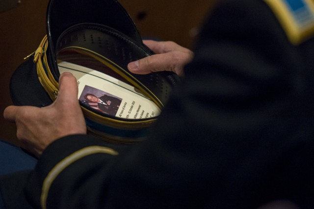 An officer holds his dress cap with a copy of Chief Warrant Officer 5 Mary Alice Hostetler's program during her retirement ceremony at the Women's Military Memorial in Arlington Cemetery on Jan. 7. Hostetler enlisted into the Army in July 1976 and was promoted to CW5 in April 2013 as the Command Chief Warrant Officer of the 200th Military Police Command. Hostetler served more than 40 years in the United States Army. Hostetler accomplished many milestones, from being the first female in a military police company, the first female to provide protective services in a combat zone, to leading a team in charge of protecting the Secretary of Defense. Hostetler says of all the things she's done in her career, the best thing she's ever done was wear the Army uniform. (Army Reserve Photo By: Sgt. 1st Class Sun Vega)