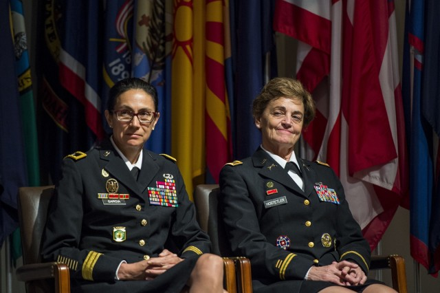 Brig. Gen. Marion Garcia, commanding general, 200th Military Police Command and Chief Warrant Officer 5 Mary Alice Hostetler listen to one the speakers at the Women's Millitary Memorial on Jan. 7 in Arlington, Virginia. Hostetler enlisted into the Army in July 1976 and was promoted to CW5 in April 2013 as the Command Chief Warrant Officer of the 200th Military Police Command. Hostetler served more than 40 years in the United States Army. Hostetler accomplished many milestones, from being the first female in a military police company, the first female to provide protective services in a combat zone, to leading a team in charge of protecting the Secretary of Defense. Hostetler says of all the things she's done in her career, the best thing she's ever done was wear the Army uniform. (Army Reserve Photo By: Sgt. 1st Class Sun Vega)