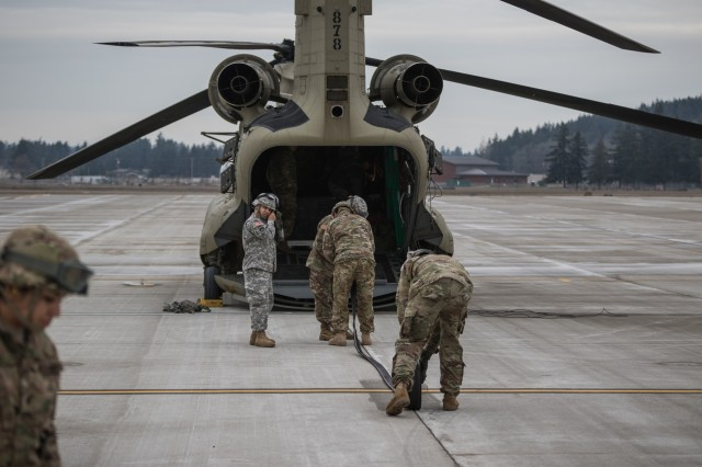 U.S. Army Soldiers assigned to 16th Combat Aviation Brigade, 7th Infantry Division roll hoses out of a U.S. Army Reserve CH-47 Chinook helicopter during training at Joint Base Lewis-McChord, Wash., Jan. 26, 2017. The Soldiers used the Forward Area Refueling Equipment to refuel Uh-60 Black Hawk helicopters in order to increase their proficiency before their upcoming mission in Afghanistan.