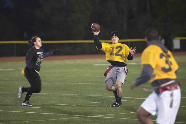 Michael Warrington, 517th Training Group quarterback (#12), passes to K.C. Marshall (right) while Co. A, 229th MI Battalion's Rachel Bourgeois (left) rushes the passer during Co. A's 20-0 flag football championship win Jan. 26.