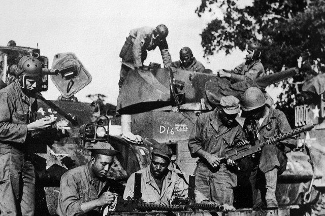 Soldiers from Dog Company of the 761st Tank Battalion check equipment before leaving England for combat in France in the fall of 1944. The 761st Tank Battalion was the first African-American tank battalion to go into battle. While most of the companies used M4 Sherman tanks, Dog Company used lighter M3 Stuart tanks and served as the reconnaissance arm of the battalion. When the unit's supply trucks became useless due to the icy, snowy weather that winter, Dog Company also began to transport supplies and wounded Soldiers.