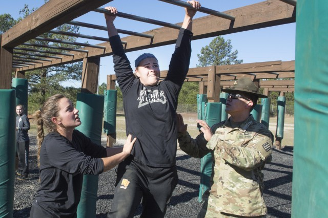 Freshman midfielder Ellie Marindin, left, with the help of Staff Sgt. Jeremy L. Jackson of Alpha Company, 1st Battalion, 13th Infantry Regiment, steadies team mate Nicole Beatson,  a freshman attacker, as she navigates the monkey bars at Fort Jackson's Fit to Win 2 course. The Women's Lacrosse Team from Winthrop University was on post Jan. 28 to learn teamwork and leadership through mental and physical challenges (U.S. Army photo by Robert Timmons, Fort Jackson Public Affairs/Released).