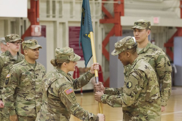 Capt. Laura Goulet (left), assumes leadership of Headquarters and Headquarters Detachment, 2nd Information Operations Battalion, 1st Information Operations Command (Land) as she receives the guidon from Lt. Col. John Whitfield, Jr. during the change of command ceremony at Wells Field House, Jan. 26.