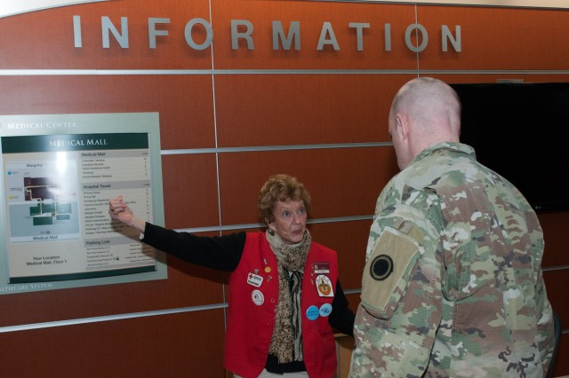 Pat Trobaugh, an American Red Cross information desk volunteer at the Madigan Army Medical Center, give Sgt. Kelly Wiebe, a video broadcast specialist with the 5th Mobile Public Affairs Detachment, directions within the hospital on Joint Base Lewis-McChord, Washington, Jan. 18. The Red Cross volunteer program at Madigan aims to provide quality of care and comfort to ill or injured service member or veteran and their families. (U.S. Army photo by Sgt. David N. Beckstrom, 5th Mobile Public Affairs Detachment, I Corps)
