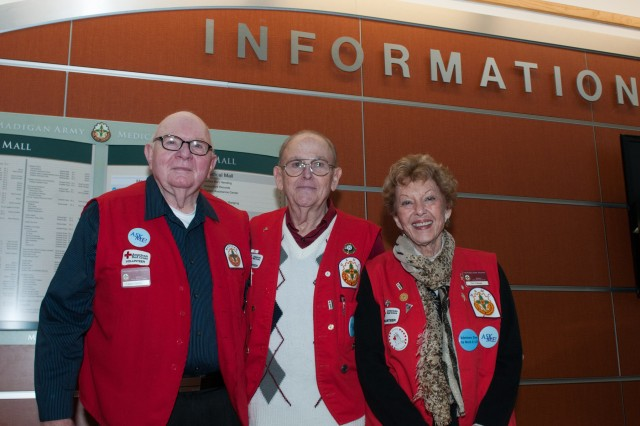 (From left to right) Gary Leakes, Aldro Grieco, and Pat Trobaugh, volunteers with the American Red Cross Madigan Army Medical Center Volunteer Program, pause for a photo near the front information desk of the Madigan Joint Base Lewis-McChord, Washington, Jan. 18. The Red Cross volunteer program at Madigan aims to provide quality of care and comfort to ill or injured service member or veteran and their families.  (U.S. Army photo by Sgt. David N. Beckstrom, 5th Mobile Public Affairs Detachment, I Corps)