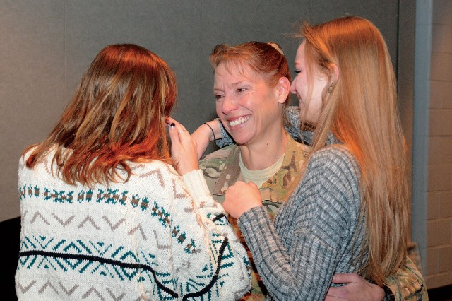Army Col. Beth Prekker greets her daughters, Lindsay and Caroline, during her surprise return from Iraq at Cosby High School in Midlothian, Va., Jan. 5, 2016.