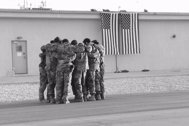 Soldiers of Special Forces, 10th Special Forces Group (Airborne) huddle together for strength as they memorialize two of their fallen brothers during a memorial held at Kunduz Airfield in Afghanistan on Nov. 7, 2016. Maj. Andrew Byers, the commander,, and Sgt. 1st Class Ryan Gloyer, an intelligence sergeant, were killed in action during the Battle of Boz Qandahari, Afghanistan, on Nov. 2-3, 2016.