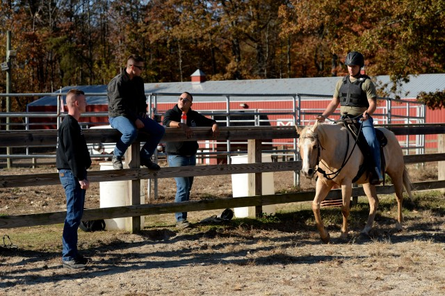 Senior instructor for the basic horsemanship course Sgt. Jake Kausen (on the left) and fellow trainers observe a trainee riding a horse at the Caisson stables at Fort Belvoir, Va., Nov. 17, 2016