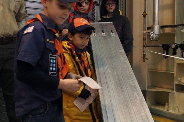 The Pinewood Derby had plenty of action and ample support from the Scouts and their leaders. Here Landon McKinnon (foreground), Adam Armstrong  (yellow jacket), Assistant Tiger Den Leader Jeb McKinnon (left), James Strickland (center rear) and Connor Cruz.