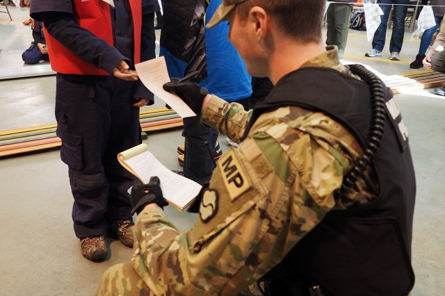 Pfc. Duncan Beardsley, of 557th Military Police Company, issues one of two speeding tickets to Cub Scout Joe Esparza at the Jan. 21 Pinewood Derby. This was the second year in a row the MPs handed out tickets for speeding to the Pinewood Derby racers.