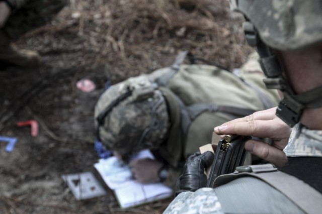 Spc. Kris McCarrick, an infantryman with the 2nd Brigade Combat Team, 82nd Airborne Division working as a student at the XVIII Airborne Corps and Fort Bragg NCO Academy, plans a tactical operation with other Soldiers while loading blank rounds for his weapon in a training area outside of Fort Bragg N.C., Jan. 30, 2017. The school, which trains Soldiers from Specialist to Staff Sergeant, helps teach the fundamentals of Army leadership.