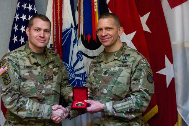 Master Sgt. Vince Lowery (left), civil affairs non-commissioned with I Corps, accepts the Army Press coin from I Corps Command Sgt. Maj. Michael Grinston, Feb. 2. Lowery was presented with the coin for an essay he penned that examined how the Army could better implement United Nations Security Council Resolution 1325, a resolution that addresses the impact armed conflict has on women.