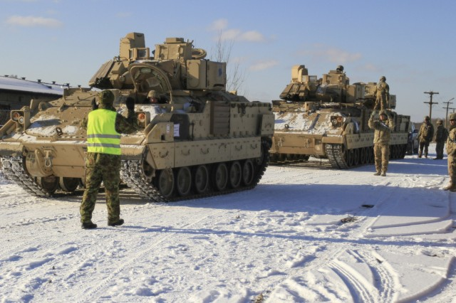 CAMP ADAZI, Latvia - An Estonian soldier helps ground guide an M2A3 Bradley Fighting Vehicle manned by Soldiers of 1st Battalion, 68th Armor Regiment, 3rd Armored Brigade, 4th Infantry Division, during railhead operations in Tapa, Estonia, Feb. 6, 2017. The vehicles arrived from Poland to support 1-68 AR, during their 9-month rotation in support of Operation Atlantic Resolve, a U.S. led effort in Eastern Europe that demonstrates U.S. commitment to the collective security of NATO and dedication to enduring peace and stability in the region. (U.S. Army photo by Sgt. Lauren Harrah/Released)