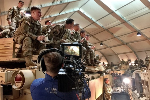 Soldiers from 1st Battalion, 8th Infantry Regiment, 3rd Armored Brigade Combat Team, 4th Infantry Division, watch the Super Bowl as a film crew from production company FILM45 captures images of them during a viewing party at Camp Karliki, Zagan, Poland, Feb. 5, 2017. The Soldiers were filmed as part of a 90-second commercial by Hyundai to pay tribute to service members on deployment. The advertisement aired on Fox immediately after the game.