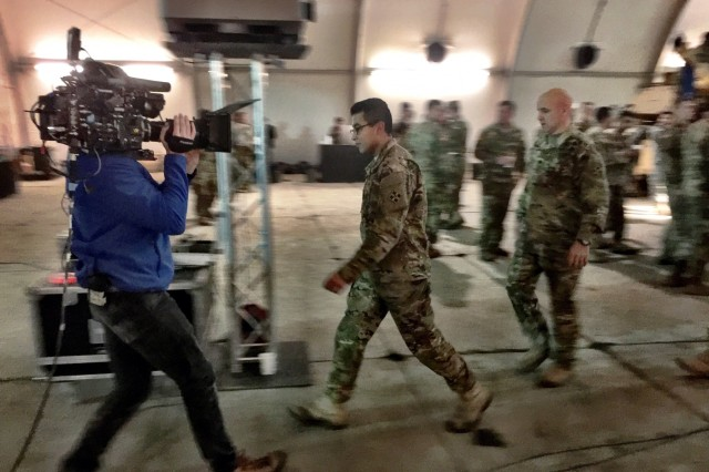 Spc. Erik Guerrero, an M1 armor crewman with Company C, 1st Battalion, 8th Infantry Regiment, 3rd Armored Brigade Combat Team, 4th Infantry Division, is led to a virtual-reality chamber by his battalion commander, Lt. Col. Jason Sabat, to watch the first half of the Super Bowl in an immersive experience, as a film crew from production company FILM45 films him during a viewing party at Camp Karliki, Zagan, Poland, Feb. 6, 2017. Guerrero's virtual reality experience included a surprise reveal -- his family was at the game -- as part of a 90-second commercial by Hyundai to pay tribute to service members on deployment. The advertisement aired on Fox immediately after the game.