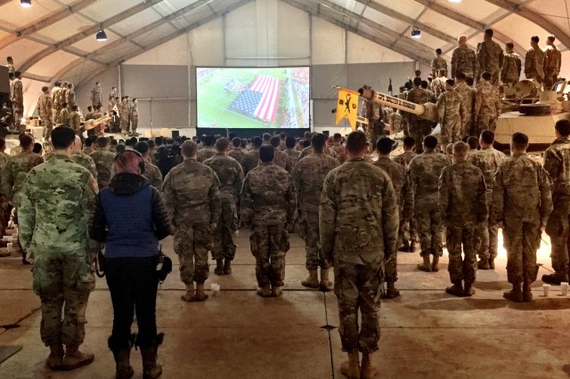 Soldiers of 1st Battalion, 8th Infantry Regiment, 3rd Armored Brigade Combat Team, 4th Infantry Division, stand at attention as the national anthem for Super Bowl LI plays on a giant screen  during a viewing party at Camp Karliki, Zagan, Poland, Feb. 6, 2017. The party was filmed as part of a 90-second commercial by Hyundai to pay tribute to service members on deployment. The advertisement aired on Fox immediately after the game.