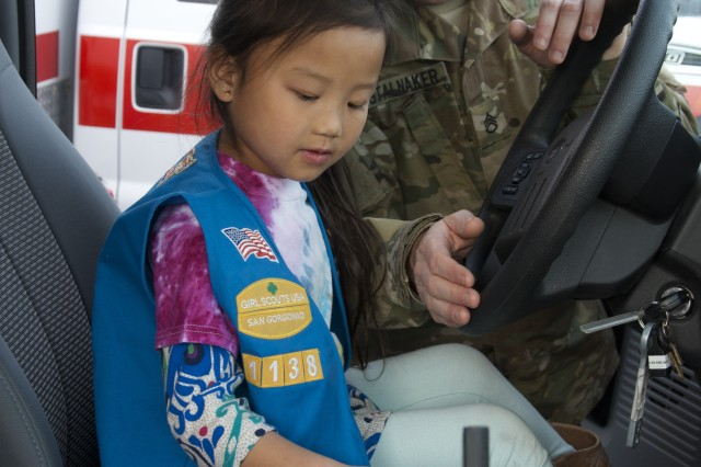 SSG Robert Stalnaker, NCOIC of the Weed Army Community Hospital Emergency Department, talks to Fort Irwin Girl Scouts Daisy Troop 1138 during the girls' recent tour of an ambulance at the hospital. The girls earned a badge for visiting and learning about emergency medical services.