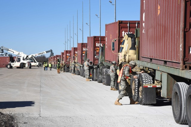 Truck drivers from the 1345th Transportation Company, Mustang, Okla., prepare their rigs for offload at McAlester Army Ammunition Plant, Okla., Jan. 26. The 70 containers of War Reserve Stocks for Allies-Korea munitions delivered to McAlester Army Ammunition Plant, Okla., will be refurbished and recycled for future use.