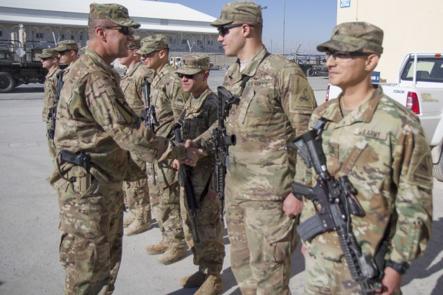 Maj. Gen. John C. Thomson III gives coins to Soldiers from Charlie Company, 1-67 AR, 1st Armored Division at Kandahar Airfield, Afghanistan before they redeploy to Kuwait to complete their 9 month rotation.