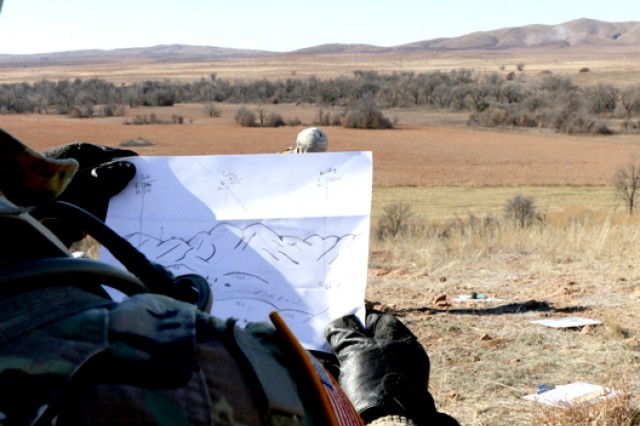 Pvt. Kenny Dixon, B/1-78th FA, holds up the terrain map he drew of Signal Mountain during live fire training for fire support specialists Feb. 1, here. The map was a quick reference and depicted the target area with landmarks, as well as direction and distance.