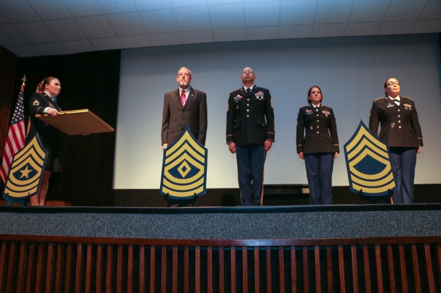 Sergeant Audie Murphy Club President, Sgt. 1st Class Jessica Stafford-Moore, presents the medallion and awards to Retired Command Sgt. Maj. Michael Roberts and Command Sgt. Maj. Thomas Latter, U.S. Army Intelligence Center of Excellence, to present to the two Soldiers being inducted into the SAMC Feb. 2 at Fitch Auditorium.  (Photo Credit: Fort Huachuca Public Affairs Lara Poirrier)
