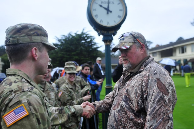 PRESIDIO OF MONTEREY, Calif. -- Larry the Cable Guy shakes hands while speaking with Pvt. Isaac Jenkins, 229th Military Intelligence Battalion, at the Pebble Beach Golf Links practice putting green prior to the 3-M Celebrity Challenge charity event, Feb. 8.