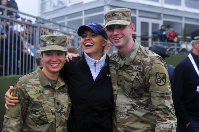 PRESIDIO OF MONTEREY, Calif. -- Spc. Amy Cloud (left) and Pfc. Kaleb Barnes take a picture with Sports Illustrated swimsuit model and Baywatch film actress Kelly Rohrbach during the 3-M Celebrity Challenge charity event at Pebble Beach, Feb. 8.